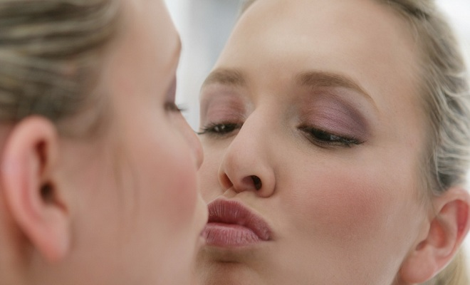 Young woman kissing mirror.